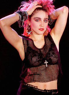 Madonna in the 80s wearing mesh vest, floral lace bra and crucifix necklace